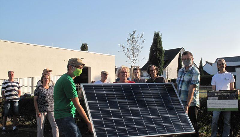 Zwei Männer halten ein Solarstrom-Modul, dahinter versammeln sich BUND-Mitglieder und Gäste.