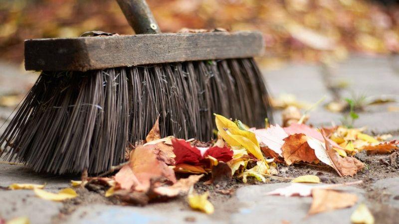 Herbstlaub mit Straßenbesen wegkehren
